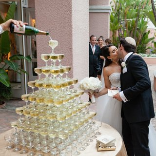 champagne-tower-with-coupe-glasses-bride-in-monique-lhuillier-dress-kisses-groom-in-yarmulke