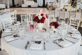 wedding-reception-white-linens-small-arrangement-of-white-flowers-and-red-florals-tapered-candles