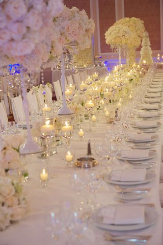 floating-candles-and-white-flower-centerpieces-on-reception-table