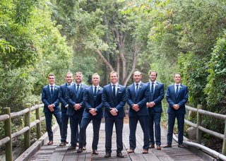 wedding-portrait-of-groom-with-groomsmen-all-in-blue-suits-and-neckties-on-wood-bridge-santa-barbara