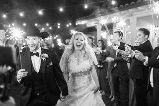 black-and-white-photo-of-bride-in-oscar-de-la-renta-dress-and-groom-cowboy-hat-during-sparkler-exit