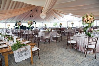 a-whimsical-tented-space-in-an-outdoor-area-with-tables-that-featured-a-secret-garden-theme-greenery