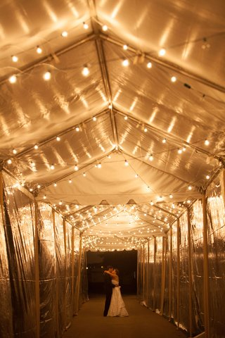 cool-couple-portrait-bright-lighting-at-night-tunnel-tent-wedding-string-lights