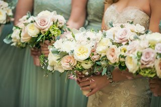 bride-and-bridesmaids-holding-white-garden-rose-light-pink-rose-green-leaves-dusty-miller-bouquet