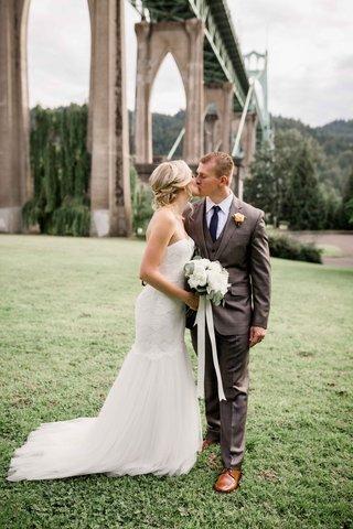 bride-groom-share-kiss-cathedral-park-portland-oregon-bridge-outdoor-wedding-rustic-chic-gray-tuxedo