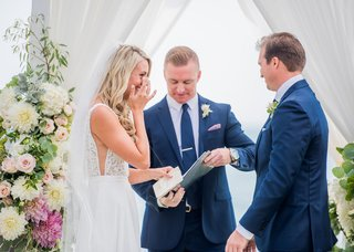 wedding-ceremony-bride-touching-eyes-crying-during-vows-groom-officiant-in-blue-suit-vow-book