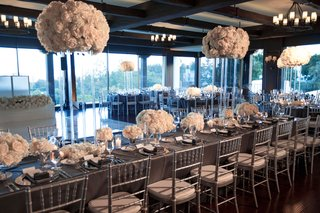 long-wedding-reception-table-floor-to-ceiling-windows-white-flower-arrangements-high-and-low-lucite