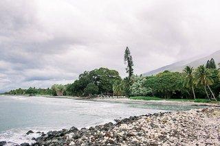 view-of-hawaiian-venue-plantation-from-sandbar-white-sand-rocky-coastline-greenery-cloudy