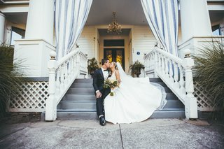 bride-in-stella-york-kissing-groom-on-porch-steps-of-white-house-napa-valley-inn