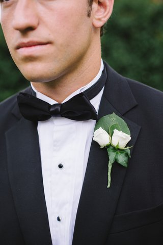 groom-in-tuxedo-wearing-two-small-roses-on-lapel