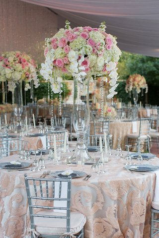 wedding-reception-with-tall-flower-arrangement-pink-white-blooms-orchids-crystals-silver-chairs