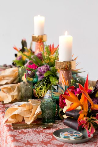 wedding-reception-table-tropical-styled-shoot-green-glassware-gold-candlestick-pink-flowers