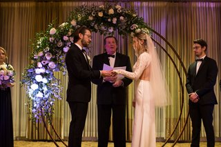 bride-and-groom-exchange-rings-circular-wedding-arch-half-covered-with-flowers-and-greenery