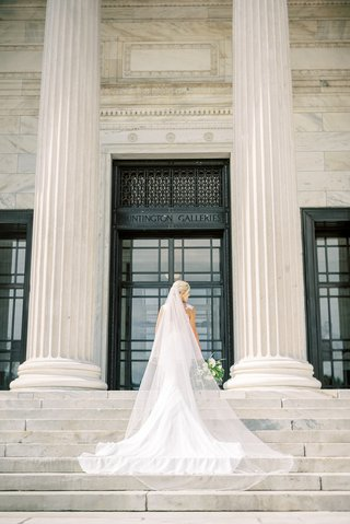 bride-in-form-fitting-pronovias-wedding-dress-wearing-cathedral-veil-on-blonde-hair-updo