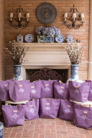 wedding-favor-welcome-bags-purple-tote-bag-with-white-monogram-fireplace-blue-white-vase-branches