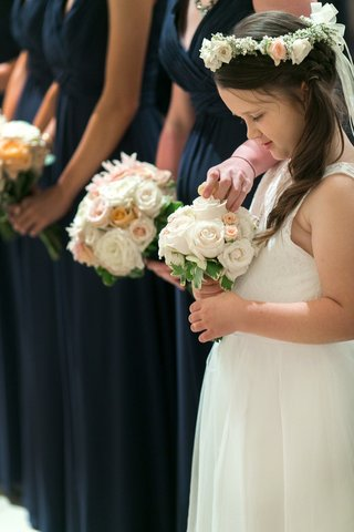 flower-girl-in-white-sleeveless-dress-small-bouquet-of-white-peach-roses-greenery-floral-halo