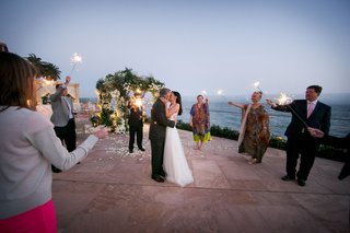 bride-and-groom-kiss-at-santa-barbara-resort-guests-holding-sparklers-sunset-kiss-wedding-ideas