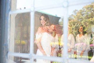 wedding-getting-ready-bridal-suite-bride-in-anne-barge-wedding-dress-bridesmaids-through-window