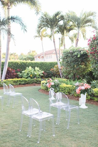 the-confused-millennial-ghost-chair-ceremony-chairs-with-tropical-arrangements-on-risers-outdoor