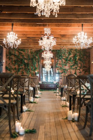 ceremony-space-wood-floor-candles-vineyard-chairs-for-guests-greenery-on-wall-chandeliers-on-ceiling