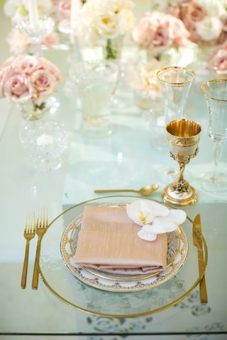 clear-gold-rimmed-charger-dusty-rose-napkin-white-orchid-gold-goblet