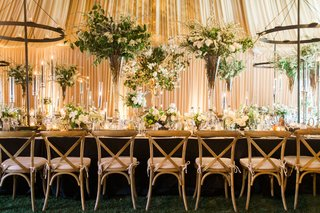 long-kings-table-wood-chairs-tall-flower-arrangements-short-high-low-rustic-chandeliers-drapes
