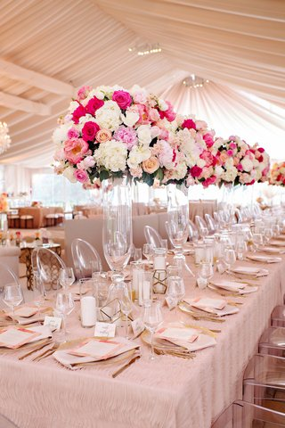 wedding-reception-tent-venue-blush-linen-on-long-head-table-ghost-chair-tall-pink-white-centerpiece