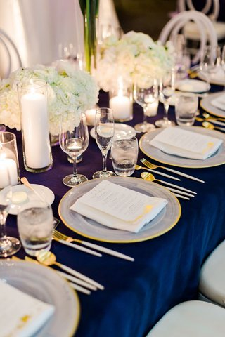 white-hydrangea-low-centerpiece-gold-rim-charger-white-gold-flatware-candles-in-vases-blue-linen