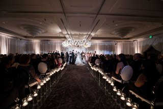 guests-taking-their-seats-at-chrome-silver-velvet-chairs-bride-and-groom-jewish-ceremony-chuppah