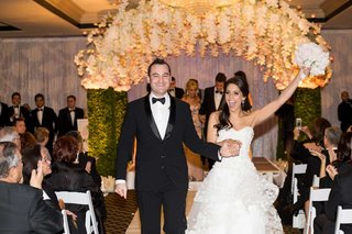 bride-in-a-strapless-monique-lhuillier-dress-and-groom-in-black-tuxedo-exit-ceremony