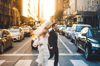 wedding-portrait-photojournalistic-image-bride-in-wedding-dress-and-veil-crossing-street-with-groom