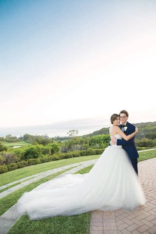 bride-in-vera-wang-ball-gown-hugging-groom-in-navy-blue-tuxedo-on-lawn-overlooking-ocean