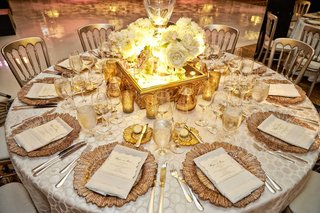 white-detailed-table-linens-with-gold-charger-plates-white-menus-small-gold-candles-mirror-stand