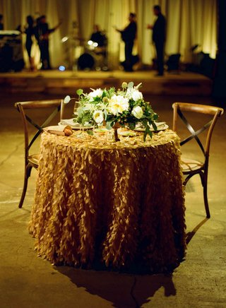 sweetheart-table-with-ruffle-linen-tablecloth-with-green-and-white-low-centerpiece-wooden-chairs