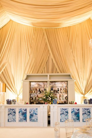 wedding-bar-at-tent-reception-blue-white-motif-clear-chairs-tent-ceiling-tall-wedding-structure
