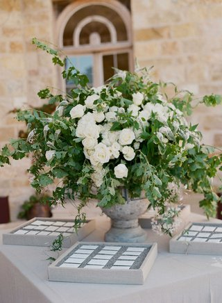 light-grey-stone-urn-white-rose-flower-arrangement-greenery-escort-cards-in-boxes-with-tan-linens