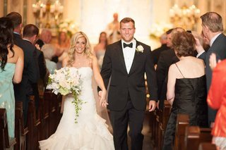 bride-in-a-strapless-lace-isabelle-armstrong-dress-holds-hands-with-brian-leonard-running-back