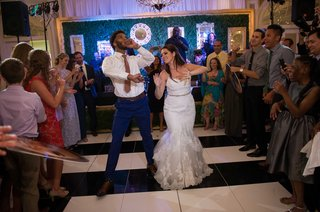 a-newlywed-couple-dances-down-an-aisle-made-by-guests-in-the-middle-of-dance-floor