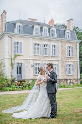 bride-in-short-sleeve-oleg-cassini-wedding-dress-champagne-flute-in-front-of-french-wedding-venue