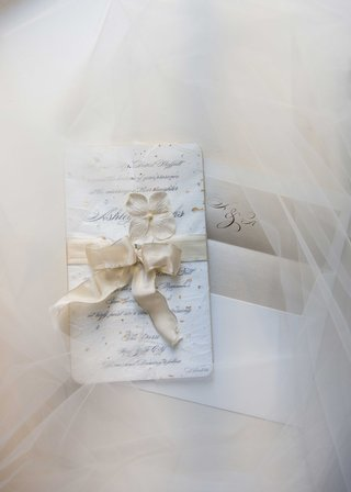 a-couples-white-wedding-invitation-with-cream-ribbon-tied-around-sits-atop-tulle