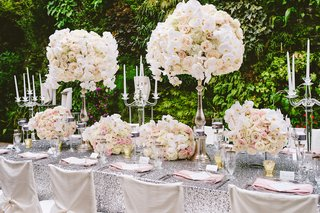 silver-sequin-tablecloths-with-white-ruffle-chair-covers-and-tall-ivory-flower-arrangements