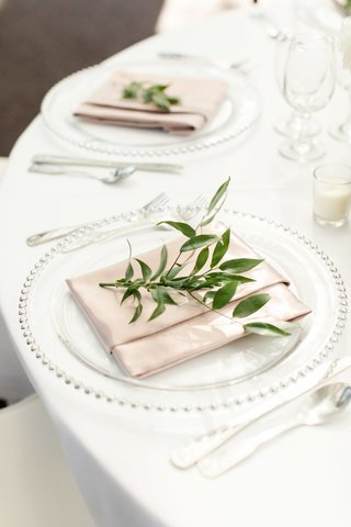 pale-blush-napkin-with-sprig-of-greenery-clear-charger-with-silver-dot-trim