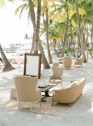 antique-style-armchair-and-sofa-on-bamboo-rug-on-sand-at-beach-wedding-cocktail-hour
