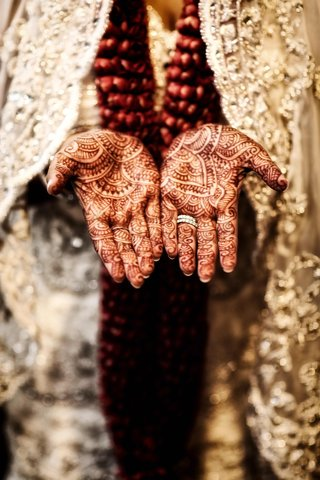 bride-wearing-wedding-rings-with-henna-on-hands