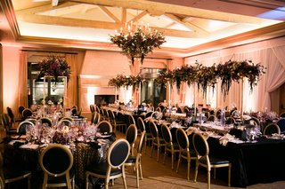 reception-space-with-black-linens-and-black-and-gold-chairs-dark-purple-florals