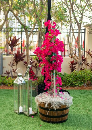 wedding-reception-tent-green-lawn-wood-basket-with-pink-bougainvillea-flowers-and-silver-lanterns
