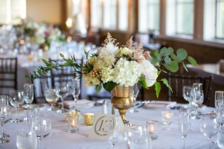 low-eclectic-floral-arrangement-gold-vessel-white-pink-flowers-green-leaves-candles