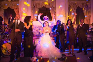 bride-and-groom-on-stage-with-wedding-band-at-reception-pink-and-purple-lighting
