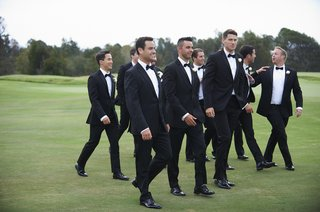 groom-with-friends-in-tuxedos-on-grass