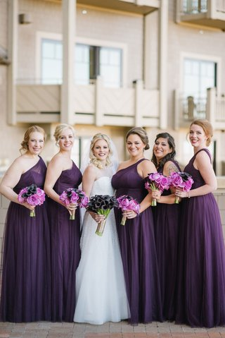 bride-in-reem-acra-wedding-dress-with-calla-lily-bouquet-and-bridesmaid-dresses-purple-one-shoulder
